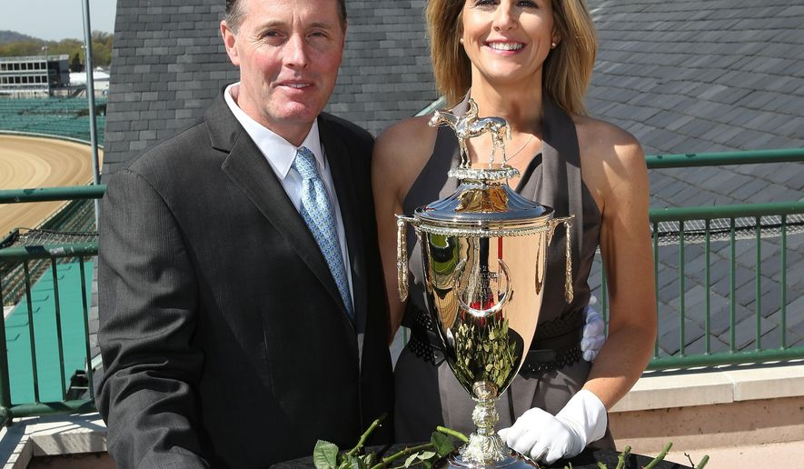 In this image provided by Churchill Downs, Artisans Bill Juaire and Susanne Blackinton-Juaire of LeachGarner, who crafted and delivered the trophy for the 142nd Kentucky Derby, pose with it at Churchill Downs, Wednesday, April 13, 2016, in Louisville, Ky. (Coady Photography/Churchill Downs via AP)