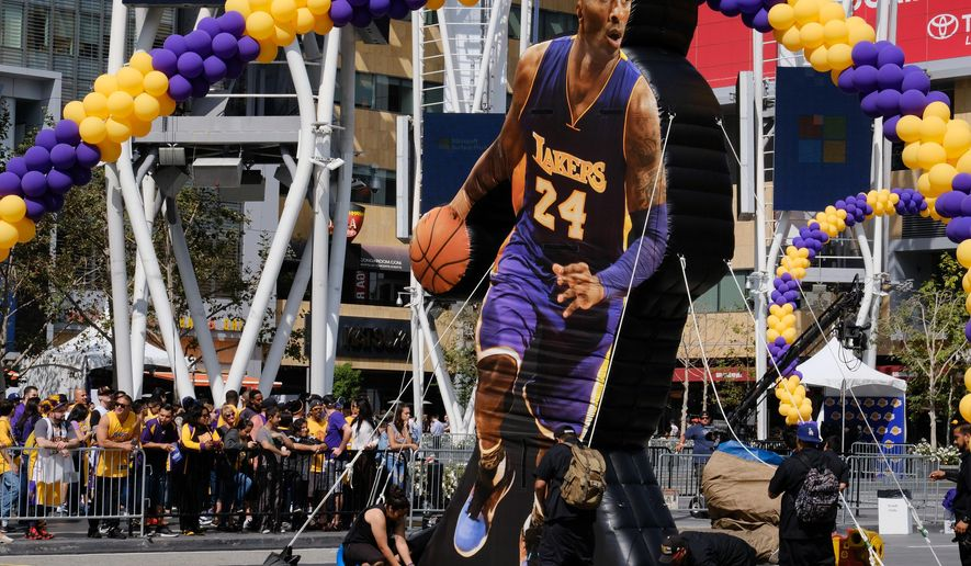 Workers set up an inflatable Kobe Bryant model for a fan festival commemorating Kobe Bryant's career outside Staples Center before his last NBA basketball game,  against the Utah Jazz, in downtown Los Angeles Wednesday, April 13, 2016. Many of Bryant's fans, even some of the adults, have never known Los Angeles without him. It's a feeling they're about to have to get used to as fans celebrate his final night as a Laker. (AP Photo/Richard Vogel)