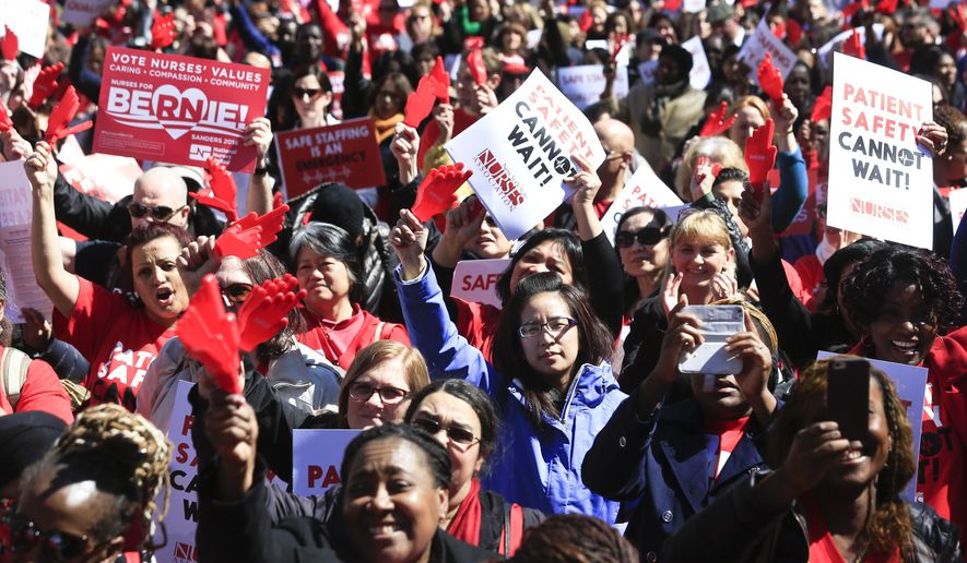 Nurses from around the state rally outside the state Capitol, Wednesday, April 13, 2016, in Albany, N.Y. Nearly 2,000 nurses are urging lawmakers to pass a minimum staffing law that would mandate how many nurses are on duty at hospitals and nursing homes.(AP Photo/Mike Groll)