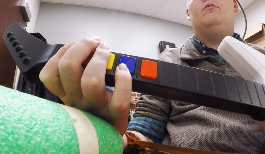 In this March 2016 photo provided by Ohio State University, Ian Burkhart plays a guitar video game as part of a study with neural bypass technology at The Ohio State University Wexner Medical Center in Columbus. A computer chip in Burkhart's brain reads his thoughts, decodes them, then sends signals to a sleeve on his arm, that allows him to move his hand. (Clark Powell/Ohio State University Wexner Medical Center via AP)