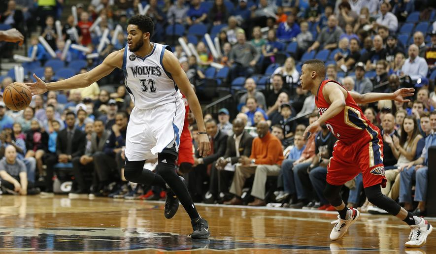 Minnesota Timberwolves center Karl-Anthony Towns (32) grabs a loose ball from New Orleans Pelicans guard Tim Frazier (2) in the first half of an NBA basketball game Wednesday, April 13, 2016, in Minneapolis. (AP Photo/Stacy Bengs)