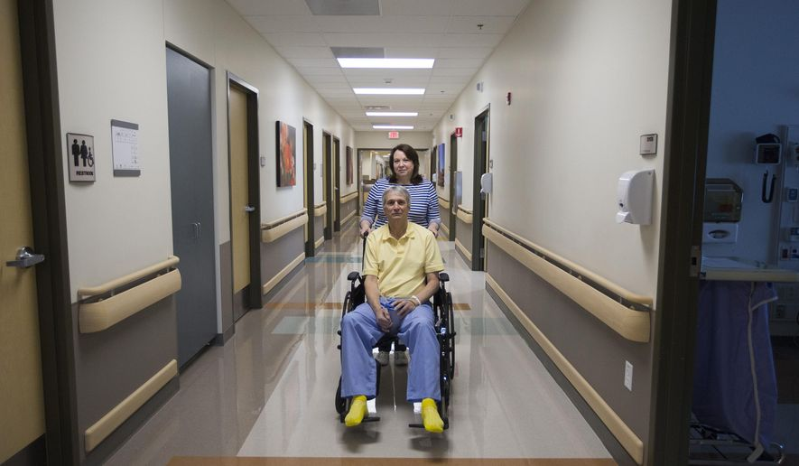 In this Feb. 18, 2016 photo, Mark Torbett and his wife, Regina, pose for a portrait at Northern Utah Rehabilitation Hospital in South Ogden, Utah. Torbett has filed a federal lawsuit against Ogden City, the Ogden Police Department and three officers. over what he says was excessive force and a violation of his Second Amendment rights by Ogden police officers during a Feb. 8 traffic stop. (Briana Scroggins/Standard-Examiner via AP) MANDATORY CREDIT