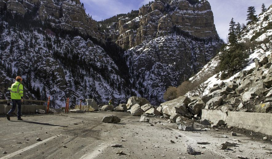 File- In this Feb. 17, 2016, file photo, a Colorado Department of Transportation worker examines debris from a rock slide on Interstate 70 in Glenwood Canyon east of Glenwood Spring, Colo. All lanes of the interstate were reopened Wednesday, April 13, 2016, after the emergency work, which tallied $5 million, was completed 23 days ahead of schedule. (Chelsea Self/Glenwood Springs Post Independent via AP, File) MANDATORY CREDIT