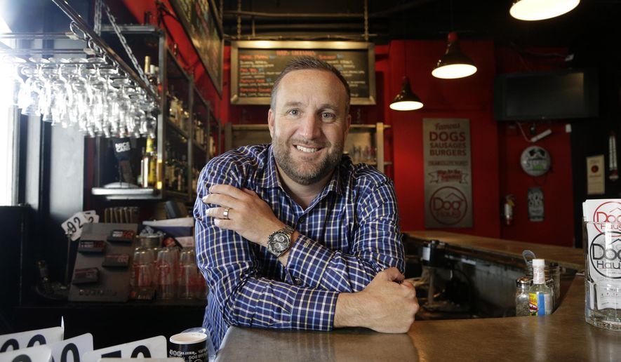 This Tuesday, April 12, 2016 photo Andre Vener, co-owner of Dog Haus, poses for a photo in his restaurant in Pasadena, Calif. In the aftermath of California and New York becoming the first states to raise the statewide minimum wage to $15, some small businesses with hourly workers are rethinking how they can absorb the increase.  The owners of Dog Haus, a chain of about 20 franchise restaurants in the West, may dispense with servers who carry food to tables and instead have customers pick up their meals at the counters in two company-owned stores. (AP Photo/Nick Ut)