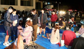 Stranded people gather outside a town hall of Mashiki, after an earthquake in Kumamoto, southern Japan, Thursday, April 14, 2016.  A powerful earthquake with a preliminary magnitude of 6.4 has struck southern Japan, collapsing walls and a number of houses.  (Kyodo News via AP)