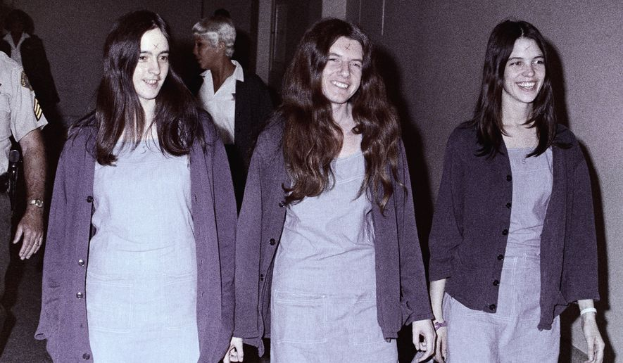 "From left, Susan Atkins, Patricia Krenwinkel and Leslie Van Houten walk to court in Los Angeles in August 1970. The three women, displaying the symbol ""X"" on their foreheads as followers of the Manson cult family, were on trial for killings including that of actress Sharon Tate. (Associated Press)"