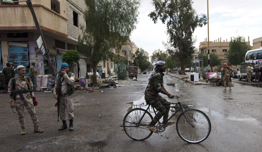 A Syrian army soldier rides his bike on a street in the Palmyra town in the central Homs province, Syria, Thursday, April 14, 2016. Russian combat engineers arrived in Syria on a mission to clear mines in Palmyra, which has been recaptured from Islamic State militants in an offensive that has proven Russia's military might in Syria despite a drawdown of its warplanes. (AP Photo/Hassan Ammar)