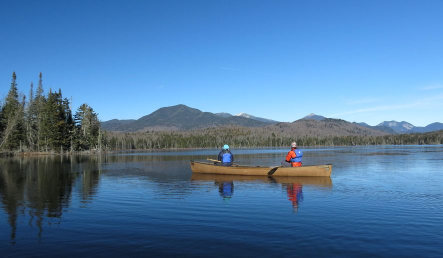 FILE - In this Nov. 17, 2015 file photo, Connie Prickett, right, of The Nature Conservancy, takes a guest on a canoe tour of Boreas Pond in North Hudson, N.Y.   A deed filed with the Essex County clerk shows New York state has purchased the 22,000-acre Boreas Ponds tract in the Adirondacks for $14.5 million. The deed was made on March 16 between the state and The Nature Conservancy and filed on April 5. A conservancy spokeswoman confirmed the purchase Thursday, April 14, 2016. (AP Photo/Mary Esch)