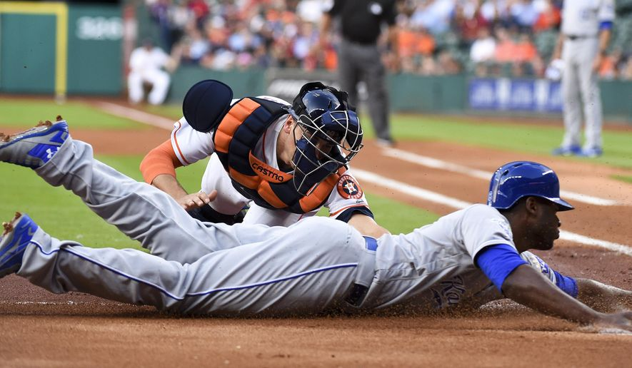 Kansas City Royals' Lorenzo Cain, right, is tagged out at home by Houston Astros catcher Jason Castro during the first inning of a baseball game Thursday, April 14, 2016, in Houston. (AP Photo/Eric Christian Smith)