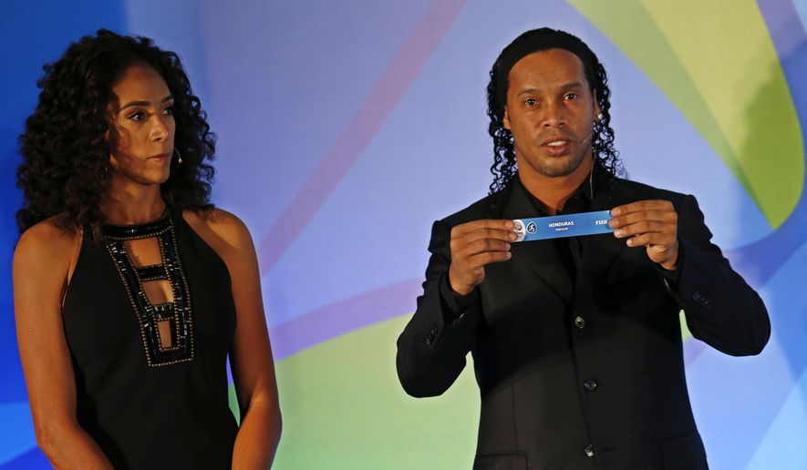 "Brazil's soccer player Ronaldinho holds a paper that reads ""Honduras,"" as he's flanked by former soccer player Aline Pellegrino during the draw for the men's Olympic football tournament in Rio de Janeiro, Brazil, Thursday, April 14, 2016.  (AP Photo/Silvia Izquierdo)"