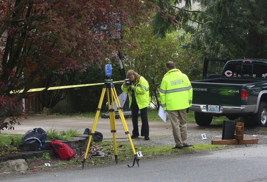 An officer takes a photo at the scene where a pickup truck slammed into children at a school bus stop in Maple Valley, Wash. (Ellen M. Banner/The Seattle Times via AP) SEATTLE OUT; USA TODAY OUT; MAGS OUT; TELEVISION OUT; NO SALES; MANDATORY CREDIT TO BOTH THE SEATTLE TIMES AND THE PHOTOGRAPHER