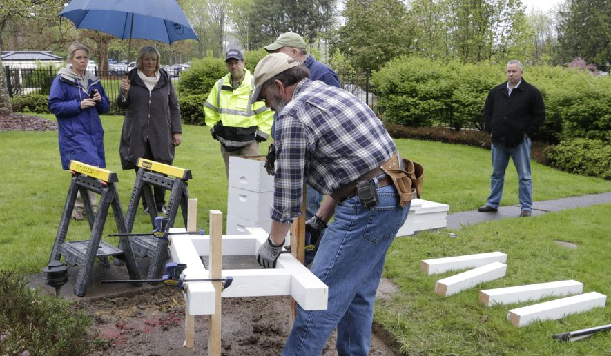 Members of the Olympia Beekeepers Association install a base for bee hive boxes on the front lawn of the governor's mansion as first lady Trudi Inslee, holding umbrella, looks on, in Olympia, Wash., Thursday, April 14, 2016. About 30,000 European honeybees will be placed in the hives next week as part of an effort to raise awareness about the decline of bee populations, as well as to boost pollination of plants on the Capitol campus. (AP Photo/Rachel La Corte)