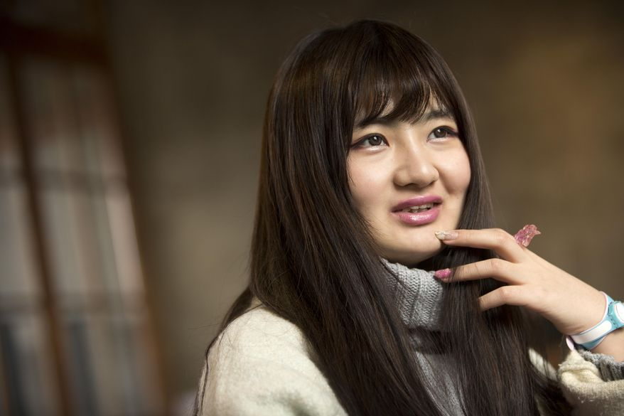 In this Feb. 28, 2016 photo, online web performer Wang Weiying, 18, speaks during an interview in Beijing. Wang has turned to one live broadcast site, Huajiao, to earn money to study abroad. She pulls in around 2,000 yuan ($310) each month for 20 hours of broadcasts, sometimes talking into her mobile phone as she walks along the street. (AP Photo/Mark Schiefelbein)