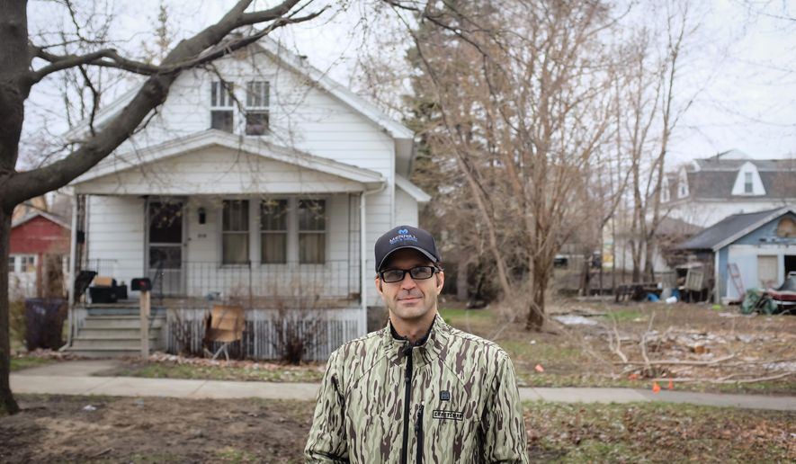 In this undated photo, Bay City Commissioner Chad Sibley, 8th Ward, poses in front of a foreclosed property in Bay City, Mich. The former Bay City commissioner who was convicted of a misdemeanor for putting a neighbor's lawn mower, grill and fire pit on the curb as part of an anti-blight effort is again seeking volunteers to help clean up the city. Chad Sibley told The Bay City Times he's organizing the second-annual cleanup day on April 23, 2016, to remove trash and rake yards of foreclosed properties that are usually off limits. (Andrew Dodson/The Bay City Times via AP) LOCAL TELEVISION OUT; LOCAL INTERNET OUT; MANDATORY CREDIT