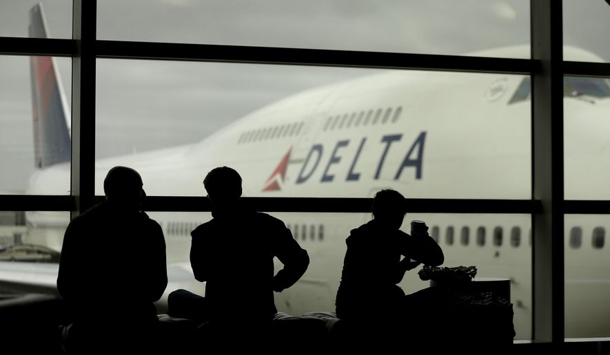 FILE - In this Monday, Oct. 29, 2012, file photo, travelers on Delta Air Lines wait for flights, in Detroit. Delta Air Lines Inc. said Thursday, April 14, 2016, it would drop the fee for U.S. consumers who buy tickets over the phone or at a ticket counter. The phone fee was $25 and the fee for a ticket bought at an airport or other ticket counter was $35. (AP Photo/Charlie Riedel, File)