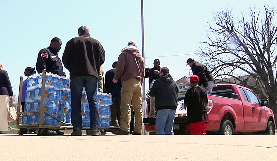 In this image made from video, volunteers from the United Auto Workers-Ford and other volunteers unload cases of water outside Sampson-Webber Leadership Academy in Detroit on Thursday, April 14, 2016. The academy is one of 19 schools in Detroit's school district that were found to have elevated levels of lead or copper in their water. (AP Photo/Mike Householder)