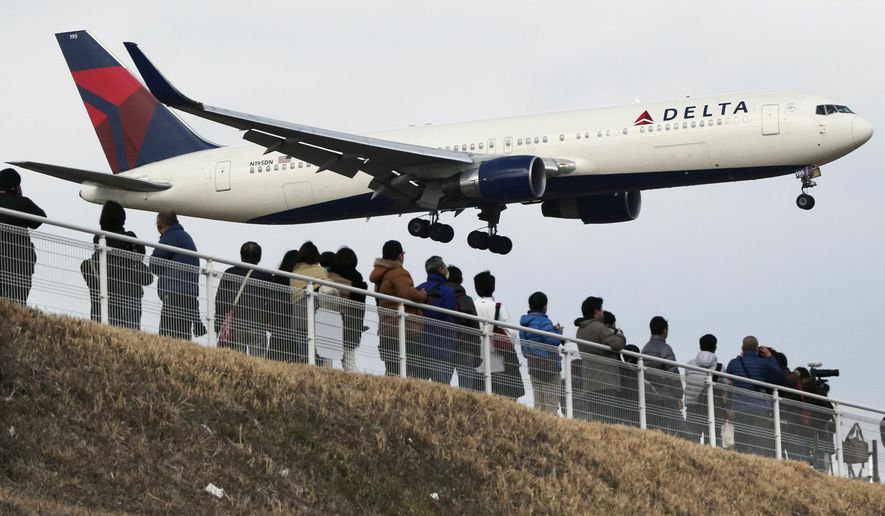 FILE - In this March 14, 2015, file photo, people watch a landing Delta Air Lines jet approach the Narita International Airport from a popular viewing spot at Sakuranoyama Park in Narita, east of Tokyo. Delta Air Lines Inc. (DAL) on Thursday, April 14, 2016, reported first-quarter profit. (AP Photo/Koji Sasahara, File)