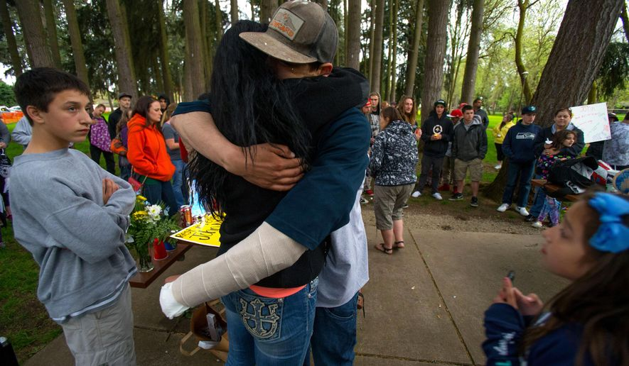 Cain Lee Barnett, 21, who suffered gunshot wounds in a murder-suicide, is embraced during a memorial service for John Mills at Emerald Park in Eugene, Ore., Wednesday, April 13, 2016. Mills, 31, was shot and killed at the park Tuesday. The shooter, Orlando Centeno, also shot and wounded Barnett, then fatally shot himself. (Brian Davies/The Register-Guard) MANDATORY CREDIT