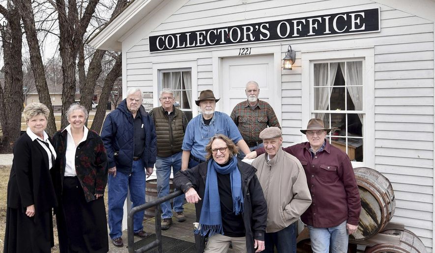 In this Feb. 29, 2016 photo, members of the Ottawa Canal Association, front row from left, Farley Andrews, Dave McBride and Arnie Bandstra and back row from left, Linda Roberts, Laura Dziedzic, Jim Mustered, Marty Ruhland, Stan Dziedzic and Bob Martyn pose for a photo in front of the toll collector's office in downtown Ottawa, Ill. The goal of group of vounteers is to re-water a section of the Illinois & Michigan Canal in downtown Ottawa and promote its tourism possibility. (Doug Larson/The Times via AP) MANDATORY CREDIT