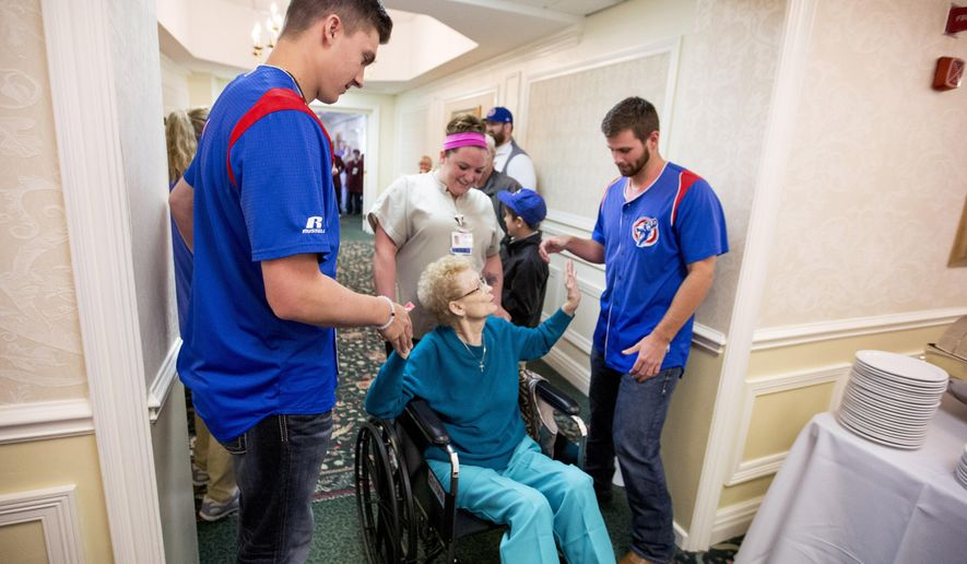 South Bend Cub's pitchers Carson Sands, left, and Craig Brooks, hi-five Nell White, 87, as she is brought in by Sanctuary at St. Paul CNA Monica Zimmer, during breakfast, Tuesday, April 12, 2016 in South Bend, Ind.  Sands and  Brooks will be living at the retirement facility as part of a partnership with Saint Joseph Health System.   (Becky Malewitz/South Bend Tribune via Becky Malewitz)