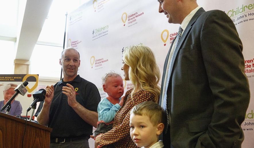 ADVANCE FOR USE SUNDAY, APRIL 17 AND THEREAFTER - In this March 30, 2016 photo, Dave Newton, program coordinator for Children's Miracle Network at St.John's Hospital, introduces 4-year-old Brenna Westlake and her family, Courtney and Evan and her brother, Connor, during a press conference in Springfield, Ill. Brenna, who suffers from a rare skin condition called Harlequin Ichthyosis, was named the Illinois Champion Ambassador for Children's Miracle Network hospitals (Rich Saal/The State Journal-Register via AP) MANDATORY CREDIT, NO SALES