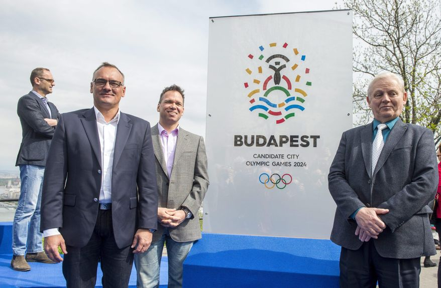 President of the Hungarian Olympic Committee Zsolt Borkai, left, Chairman of the Budapest 2024 bid Balazs Furjes, second left, and Budapest Mayor Istvan Tarlos, right, pose in front of the logo of  host city candidate Budapest for the 2024 Olympic and Paralympic Games during its presentation ceremony held on the Gellert Hill in Budapest, Hungary, Thursday, April 14, 2016. The key elements of the logo are the Statue of Liberty, center, the water and the five Olympic rings. (Tibor Illyes/MTI via AP)