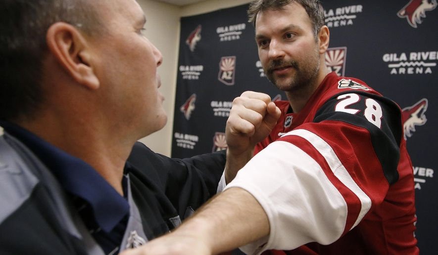 In this photo taken on Tuesday, Nov. 24, 2015, Arizona Coyotes' John Scott, right, gives Associated Press sports writer John Marshall, left, a hockey fighting tutorial, in Glendale, Ariz. The Coyotes traded Scott in January, 2016. (AP Photo/Ross D. Franklin)
