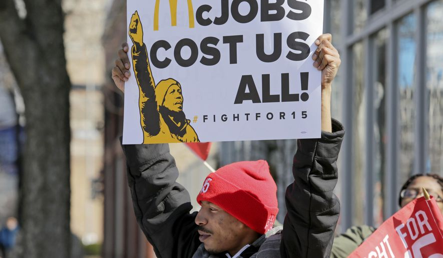 "Solo Littlejohn, a fast food worker from Cicero, Ill., joins protesters calling for a union and pay of $15 an hour outside a McDonald's restaurant in Chicago on Thursday, April 14, 2016. The ""Fight for $15"" is part of an ongoing push targeting the world's biggest hamburger chain. (AP Photo/Teresa Crawford)"