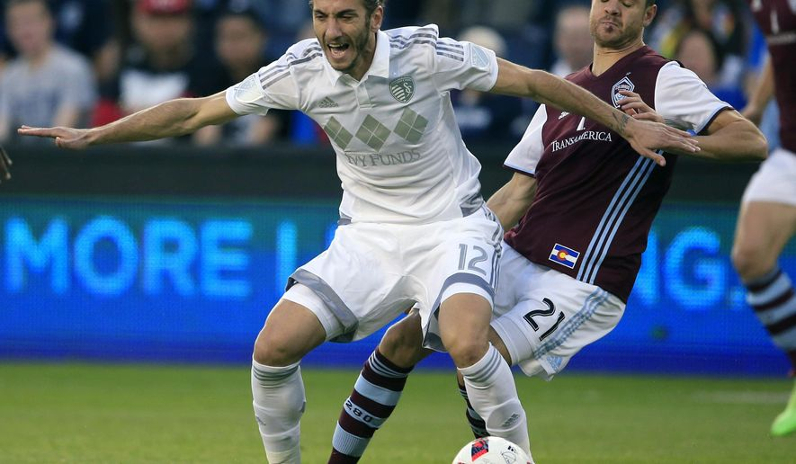 Sporting Kansas City defender Nuno Coelho (12) is covered by Colorado Rapids forward Luis Solignac (21) during the first half of an MLS soccer match in Kansas City, Kan., Wednesday, April 13, 2016. (AP Photo/Orlin Wagner)