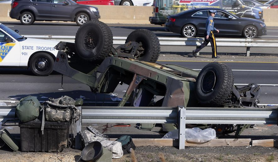 A state police trooper works the site where a Humvee overturned on the New Jersey Turnpike in South Brunswick, N.J., Thursday, April 14, 2016. State police said at least four soldiers were injured after the military vehicle overturned. (Thomas P. Costello/Home News Tribune via AP) MANDATORY CREDIT