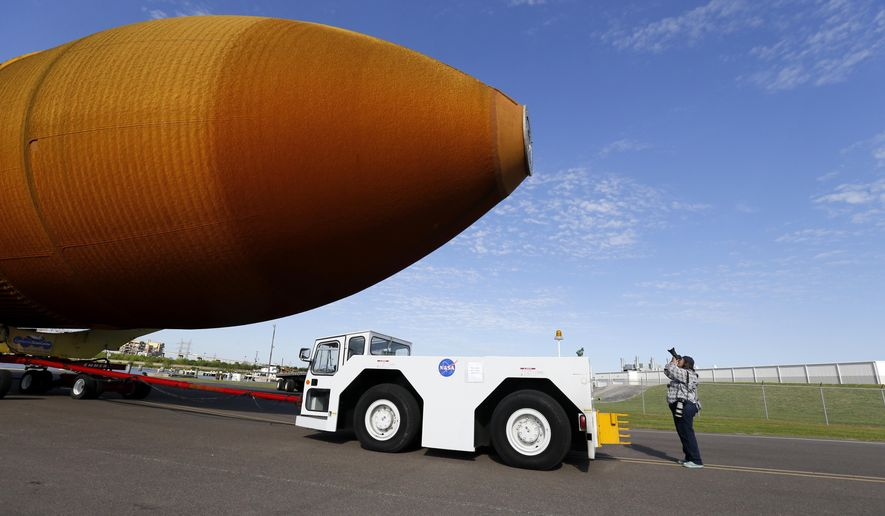 In this Sunday, April 10, 2016 photo, external Tank, ET- 94, NASA's only remaining space shuttle external tank, is transported by trailer to a dock at the NASA Michoud Assembly Facility in New Orleans. The tank is embarking on a journey, via the Gulf of Mexico and the Panama Canal, to the California Science Center in Los Angeles, as part of the Space Shuttle Endeavour display. (AP Photo/Gerald Herbert)