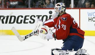 Washington Capitals goalie Braden Holtby (70) blocks a shot during the first period of Game 1 in the first round of the NHL Stanley Cup hockey playoffs against the Philadelphia Flyers, Thursday, April 14, 2016, in Washington. (AP Photo/Alex Brandon)