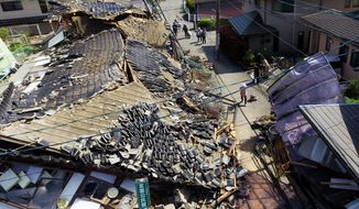 This aerial view shows damaged houses in Mashiki town, Kumamoto prefecture, southern Japan on April 15, 2016, a day after a magnitude-6.5 earthquake. More than 100 aftershocks from the first earthquake continued to rattle the region as businesses and residents got a fuller look at the widespread damage from the unusually strong quake, which also injured about 800 people. (Koji Harada/Kyodo News via AP)