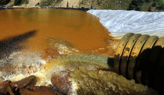 FILE - In this Aug. 14, 2015 file photo, water flows through a series of retention ponds built to contain and filter out heavy metals and chemicals from the Gold King mine chemical accident, in the spillway about 1/4 mile downstream from the mine, outside Silverton, Colo. Researchers who studied a river in Colorado after a massive mine spill say runoff from fall storms kicked up the levels of some contaminants in the water but not others. (AP Photo/Brennan Linsley, File)
