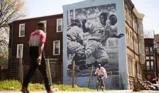People pass by a Philadelphia Mural Arts Program mural of Jackie Robinson in Philadelphia on Friday, April 15, 2016. On Jackie Robinson Day, Philadelphia is acknowledged its racist treatment of the baseball pioneer when he played in the city nearly 70 years ago. City leaders issued an official apology in March, and highlighted its official apology during a ceremony Friday, also honoring Moses Fleetwood Walker, the first black Major League player. (AP Photo/Matt Rourke)