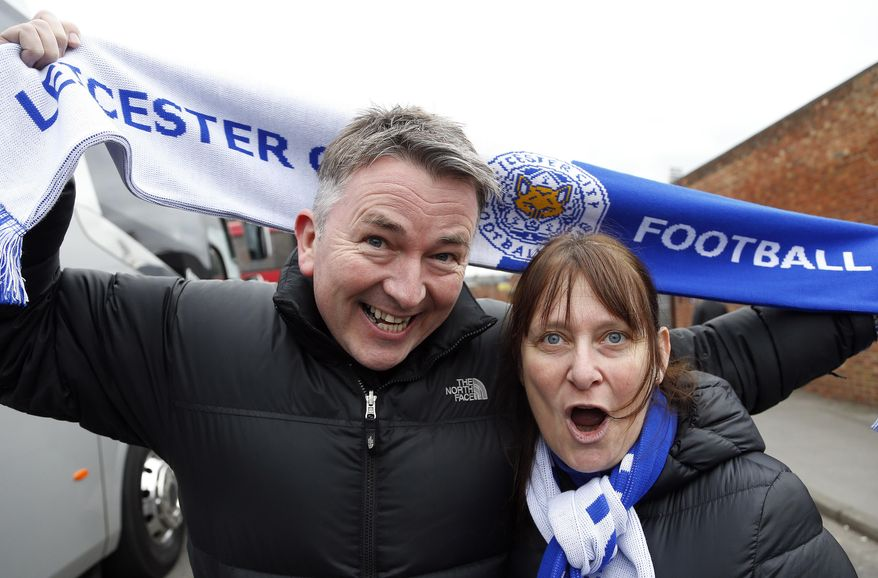 In this photo taken Saturday, March 19, 2016, English Premier League side Leicester City fans Phil and Steph Jastrzebski arrive for the English Premier League soccer match between Crystal Palace and Leicester City at Selhurst Park stadium in London. Leicester fans never expected to see their modest team have a shot at winning the Premier League this season. Phil Jastrzebski is amazed at how Leicester has soared up the standings while relying on players like Jamie Vardy and Riyad Mahrez, who collectively cost about $2 million. (AP Photo/Frank Augstein)