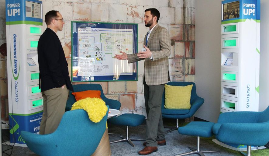 Steven Schwartz, left, and Alex Gast, right talk in the charging station during the grand opening of Consumer Energy's new Innovation Center, Friday, April 15, 2016, in Jackson, Mich. (Taylor Irby/Jackson Citizen Patriot via AP)