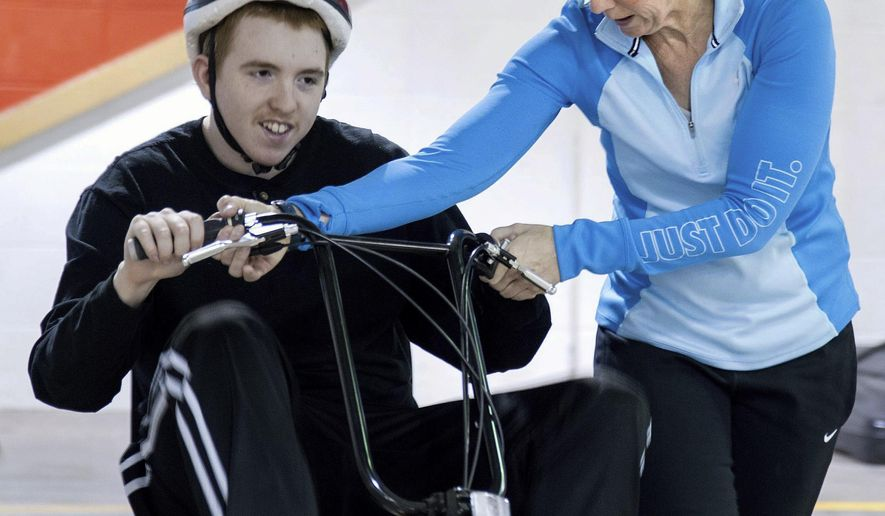 In this March 28, 2016 photo, Lori Lyons, an adaptive physical education teacher at the Vermilion Association for Special Education co-op in Tilton, Ill., helps Drew Nunn with the controls on his bike. Lyons is a member of the Danville AMBUCS, a service organization that's dedicated to creating opportunities for independence for people with disabilities. She has chaired the AMBUCS Challenger Baseball League during the 12 years of its existence. (Rick Danzl/The News-Gazette via AP) MANDATORY CREDIT