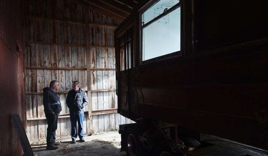 In this photo taken March 30, 2016, Jay Drouillard, left, talks with Grass Lake Supervisor Jim Stormont as a 1905 Chicago streetcar is delivered to the Scott Willis farm near Grass Lake, Mich. The interurban streetcar will be restored at the farm and will eventually be placed in the upcoming Lost Railway Museum. (J. Scott Park/Jackson Citizen Patriot via AP) LOCAL STATIONS OUT; LOCAL INTERNET OUT; MANDATORY CREDIT