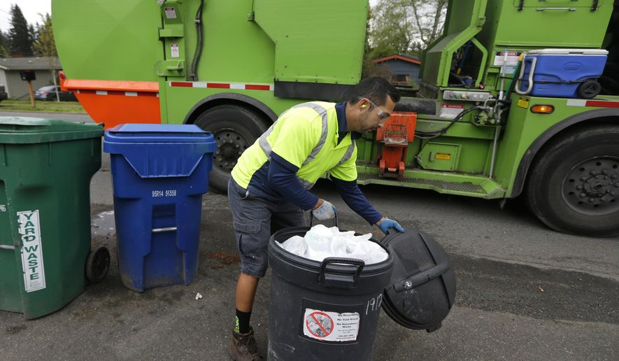 David Morales, a garbage driver with Recology, picks up a garbage container for Seattle Public Utilities, Friday, April 15, 2016, in Seattle.  A judge is scheduled to hear a challenge Friday, April 16, 2016, to a new Seattle law allowing garbage collectors to check people's trash to see whether they are disposing of recycling items and food waste incorrectly.  (AP Photo/Ted S. Warren)