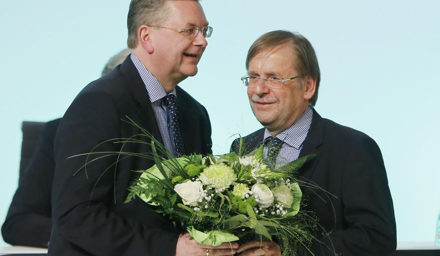 New elected President of the German Football Federation Reinhard Grindel, left, receives flowers from acting President Rainer Koch after his election during a meeting of the German Football Federation DFB in Frankfurt, Germany, Friday, April 15, 2016. (AP Photo/Michael Probst)