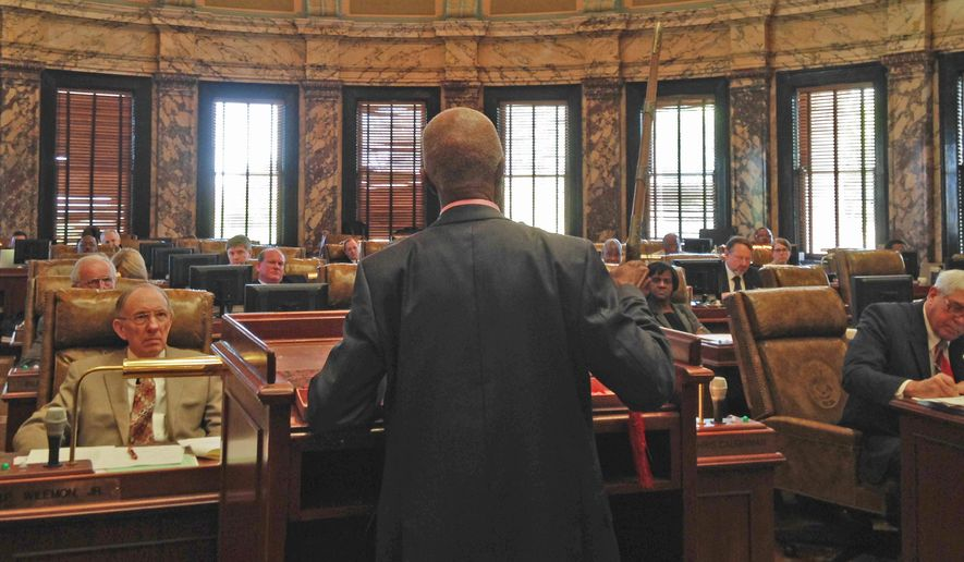 In this Tuesday, March 29, 2016 photo Sen. Hillman Frazier, D-Jackson, brandishes a sheathed sword during debate over House Bill 786, at the Capitol in Jackson, Miss. Frazier opposed the bill, which would grant immunity to trained church security teams that shoot people trying to commit violent crimes. Frazier said the bill went against Christian teaching, recounting the story of Jesus healing a servant of a high priest after a disciple cut off the servant's ear with a sword. (AP Photo/Jeff Amy)