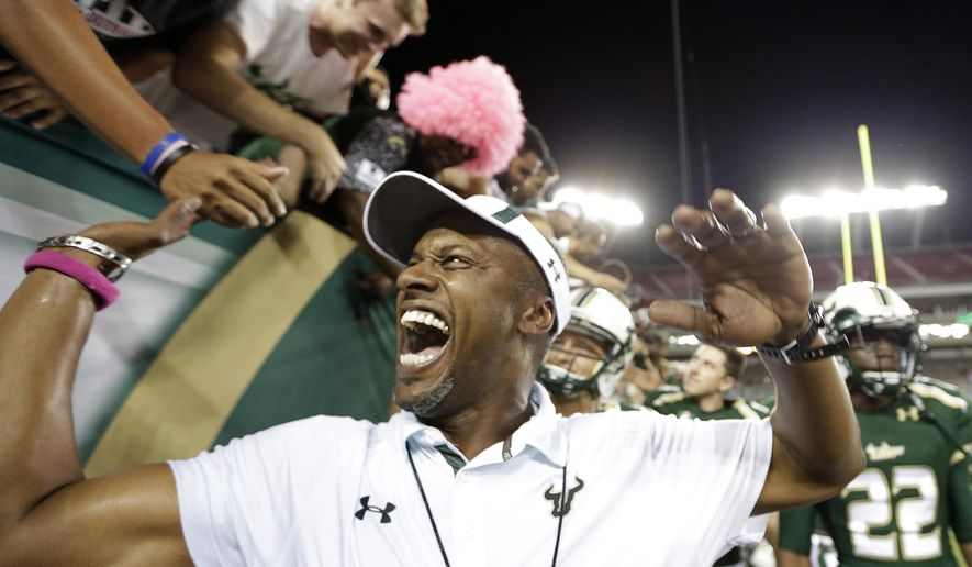 FILE - In this Oct. 5, 2015, file photo, South Florida coach Willie Taggart celebrates with fans after South Florida defeated Cincinnati 26-20 in an NCAA college football game in Tampa, Fla. After hitting rock bottom at Maryland last year, USF went 7-3, played like one of the best teams in the country outside the Power Five and Taggart went from a coach with an uncertain future to one with a three-year contract extension. (AP Photo/Chris O'Meara, File)