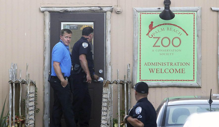 Police officers enter the administration building at the Palm Beach Zoo after zookeeper Stacey Konwiser died while being attacked by a tiger, Friday, April 15, 2016, in West Palm Beach, Fla. (Damon Higgins/Palm Beach Post via AP)