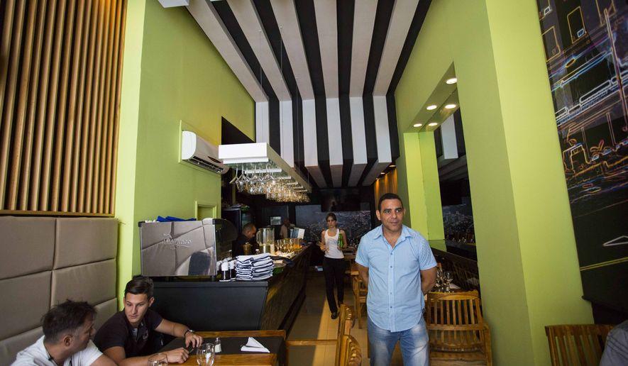 In this April 5, 2016, file photo, Reinaldo Bordon, 44, walks through his restaurant on Calle Habana in Old Havana, Cuba. (AP Photo/Desmond Boylan)