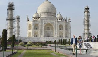 Britain's Prince William, along with his wife, Kate, the Duchess of Cambridge, walk in front of the Taj Mahal in Agra, India, Saturday, April 16, 2016. Agra is the last stop on the royal couple's weeklong visit to India and neighboring Bhutan. (Shahbaz Khan /Press Trust of India via AP)