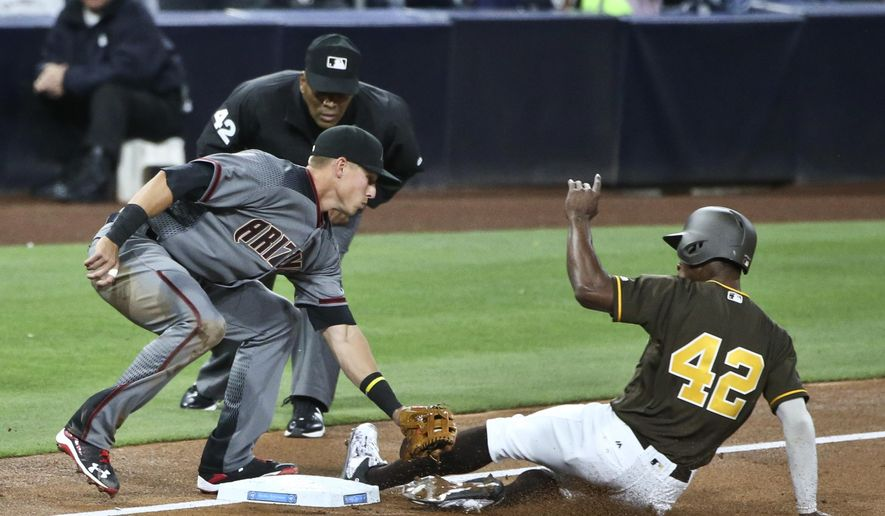 San Diego Padres' Melvin Upton Jr. s;ides under the tag of Arizona Diamondbacks third baseman Jake Lamb while stealing a base during the second inning of a baseball game Friday, April 15, 2016, in San Diego. The umpire is Laz Diaz. (AP Photo/Lenny Ignelzi)