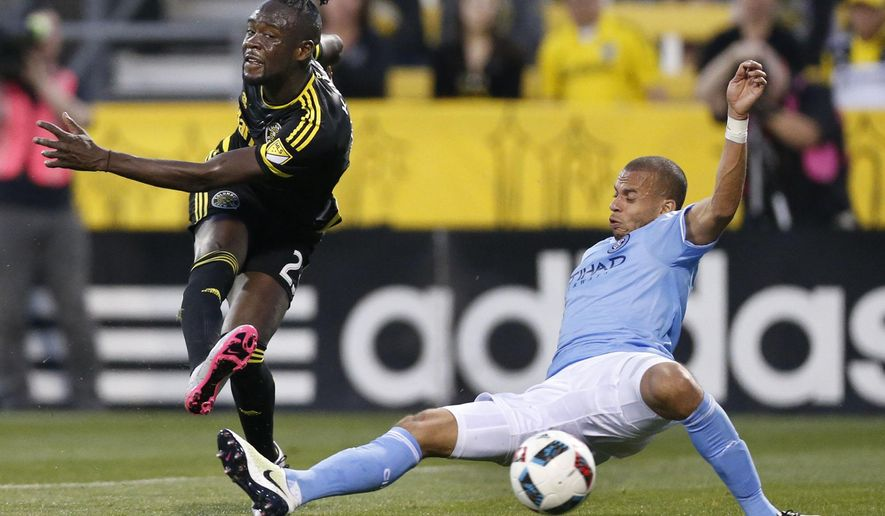Columbus Crew forward Kei Kamara, left, kicks to the goal in front of New York City FC defender Jason Hernandez during the first half of an MLS soccer game Saturday, April 16, 2016, in Columbus, Ohio. ((Fred Squillante/The Columbus Dispatch via AP)