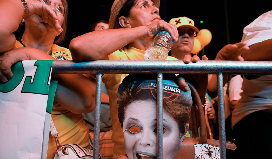 Anti-government demonstrators, one holding a mask depicting Brazilian President Dilma Rousseff, watch a large screen in Sao Paulo on Sunday as lawmakers vote on whether or not to impeach Ms. Rousseff. (Associated Press)