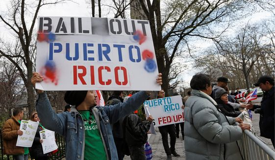 A demonstrator protests the Federal Reserve's failure to bail out Puerto Rico outside International House in New York on April 7, 2016. (Associated Press) **FILE**